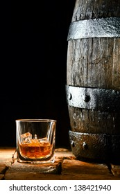 Glass of golden matured premium brandy or whiskey on the rocks alongside an old oak barrel standing upright on old bricks with a dark background