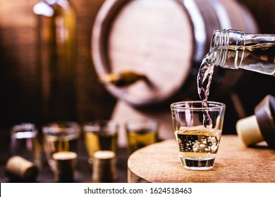 Glass of golden rum, with bottle. Bottle pouring alcohol into a small glass. Brazilian export type drink. Brazilian product for export, distilled drink known as brandy or pinga. Day of cachaça.