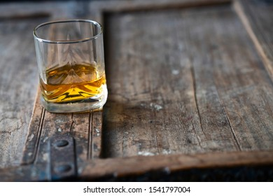 Glass with golden shimmering whisky on shabby stylish wooden furniture