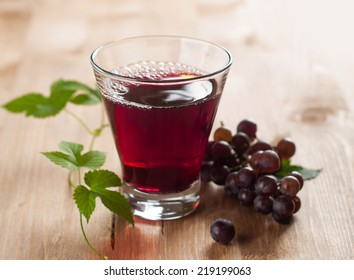 Glass of grape juice with grapes on the background, selective focus