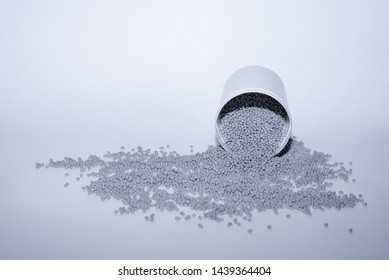 Glass with gray thermoplastic elastomer granules on white background