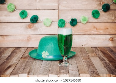 Glass of green beer with Irish festive hat on wooden background. Tabletop, side view.