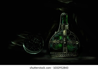 Glass green bottle with magic potion on a dark background. Magic elixir.