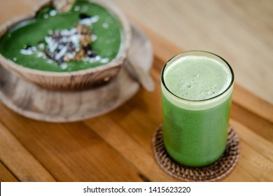 Glass of green celery juice on wooden table