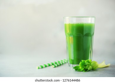 Glass of green celery smoothie on grey concrete background. Banner with copy space. Fresh juice for detox. Vegan, alkaline healthy diet concept.