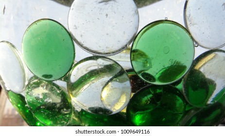Glass green and colorless flattened laterally glass beads in water and a small sink and glass splashes in the water.