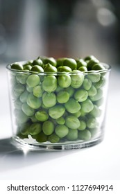 Glass of green peas on a white table