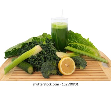 Glass of green vegetable juice with fresh vegetables on a cutting board, over white