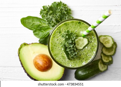 Glass of green vegetable smoothie on white wooden background from top view