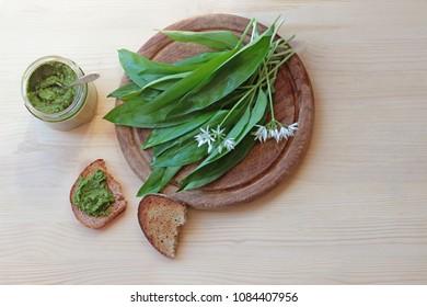 a glass with green wild garlic pesto and fresh garlic leaves on a cutting board