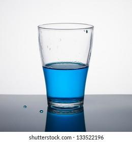 Glass half full of blue liquid on light background.