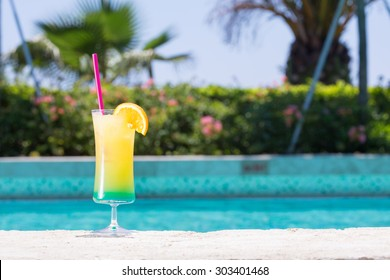 Glass of Happy days non alcohol cocktail on the pool nosing at the tropical resort. Horizontal, cocktail on left side