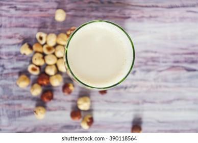 A glass of hazelnut milk and raw hazelnuts