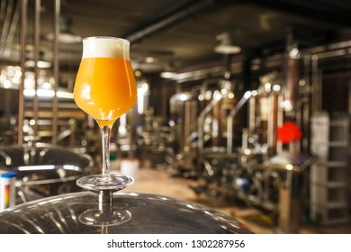 A glass of hazy IPA beer standing on a tank in a functional brewery