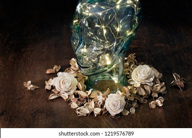 Glass head with lights inside surrounded by flowers on dark background