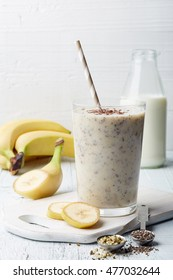 Glass of healthy banana and seeds smoothie on white wooden table