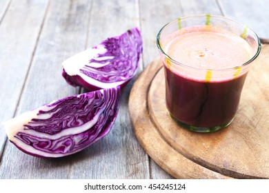 A glass of healthy purple cabbage juice with fresh sliced purple cabbage on a wooden table.