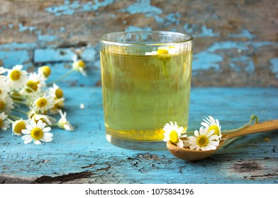 glass of herbal chamomile tea on a blue wooden table.