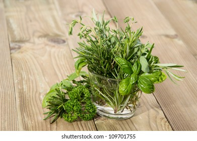 Glass with Herbs on wooden background