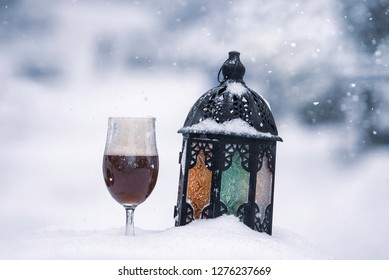 A glass of homebrewed beer, aganist a snowy background.