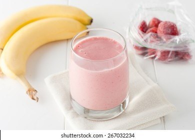 a glass of homemade banana and frozen strawberry smoothie on white background