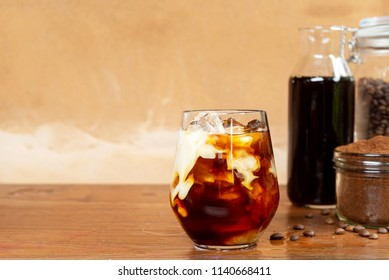 a glass of homemade cold cold brew coffee with milk on wooden table