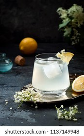 A glass of homemade elderflower gin sour or lemonade garnished with freshly picked elderflowers.