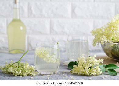 A glass of homemade elderflower lemonade with freshly picked elderflowers. The flowers are edible and can be used to add flavour and aroma to both drinks and desserts.