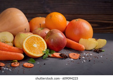 Glass of homemade juice or smoothie, fruits and vegetables. Fresh carrot, apple, pumpkin, orange, grapefruit on dark table. Healthy eating, food, dieting, detox and vegetarian concept.