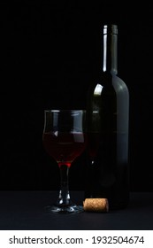 A glass of homemade wine next to a bottle on a dark background. Glass of red wine on a black background. Alcoholic drink