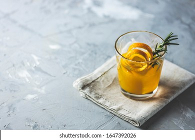 Glass of honey bourbon cocktail with rosemary simple syrup or homemade whiskey sour cocktail drink with orange and rosemary decoration orange peel on linen napkin. Light concrete surface.