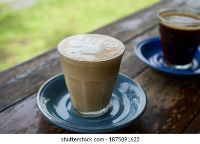 A glass of hot caffelatte with a beautiful seahorse shaped foam, close-up shots on the wooden table with blurred background.