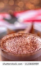 A glass of hot chocolate with a frothy top and red and white background