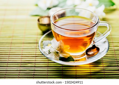 Glass of hot herbal tea on bamboo background closeup. Teacup with organic green tea and fresh jasmine flower on wooden table. Healthy alternative medicine and natural detox beverage.