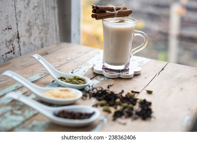 glass of hot indian yoga drink - masala chai tea with spices and igredients on a rustic table