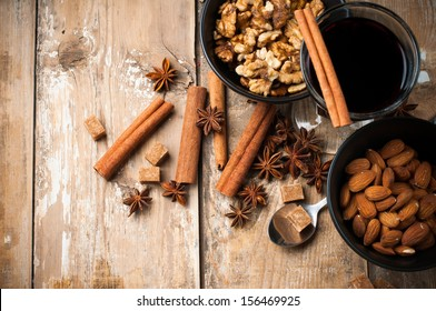 A glass of hot mulled wine, spices, cinnamon, star anise, brown sugar and nuts on a wooden board