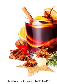 Glass with Hot red mulled wine for winter and Christmas with orange slice, anise and cinnamon sticks isolated on white background, macro