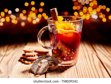 Glass of hot spicy Gluhwein with cookies on a wooden table with a backdrop of sparkling Christmas party lights
