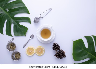 A glass of hot tea with fruit, tea infuser, spoon and leaves decorated on white background.