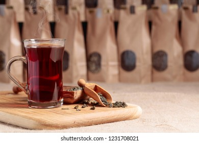 Glass of hot tea. Wooden spoon with dried tea leaves. Craft paper pack with window for loose tea. Copy space.