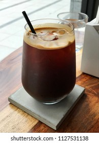 a glass of ice americano coffee with black straw on concrete coaster and wooden table, coffee shop