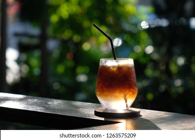a glass of ice americano tonic on wooden bar in out door coffee shop