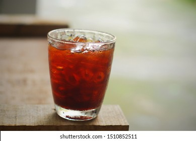 a glass of ice black coffee on wooden tables. look so fresh