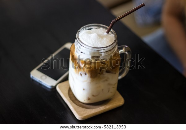 A glass of ice coffee milk Late with blurred moblie phone on table