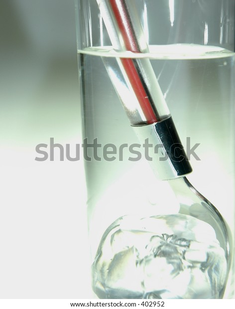 glass with ice cube and spoon