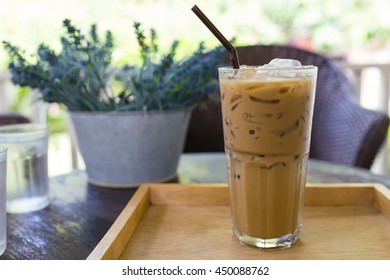 glass of ice espresso on the wooden tray with artificial flower pot  on wooden table in coffee bar