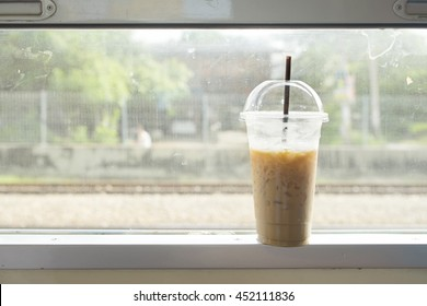 Glass of ice milk coffee on the window frame on the train in Thailand.