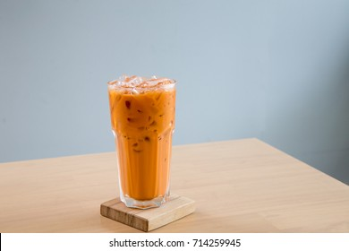 A glass of ice milk tea, fresh and sweet dessert on a wooden saucer
