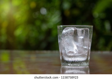 Glass with ice Put on wooden floor Green background of nature