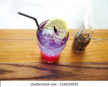 A glass of ice strawberry soda mixed with butterfly pea syrup and lemonade, decorated with sliced lemon and dried butterfly pea, Tropical mixed mocktail, Summer drink concept.